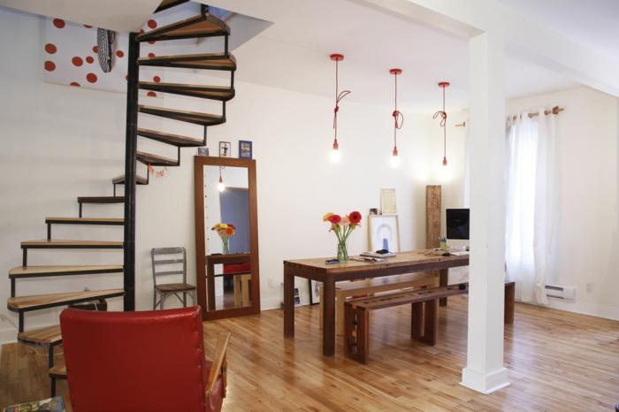escalera caracol, salón con muebles de madera, sillón rojo, bombillas colgantes, espejo grande, escalera de caracol sin barandilla
