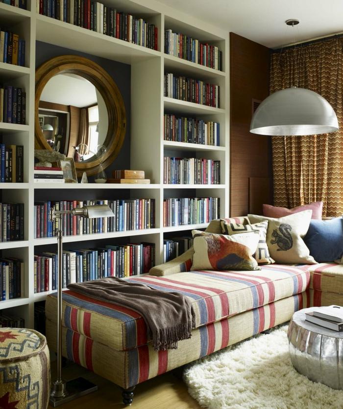 ideas de decoración, librerías, rincón de lectura, estantería de madera blanca, espejo redondo con marco de madera, sofá cama con cojines, tapete redondo peludo blanco