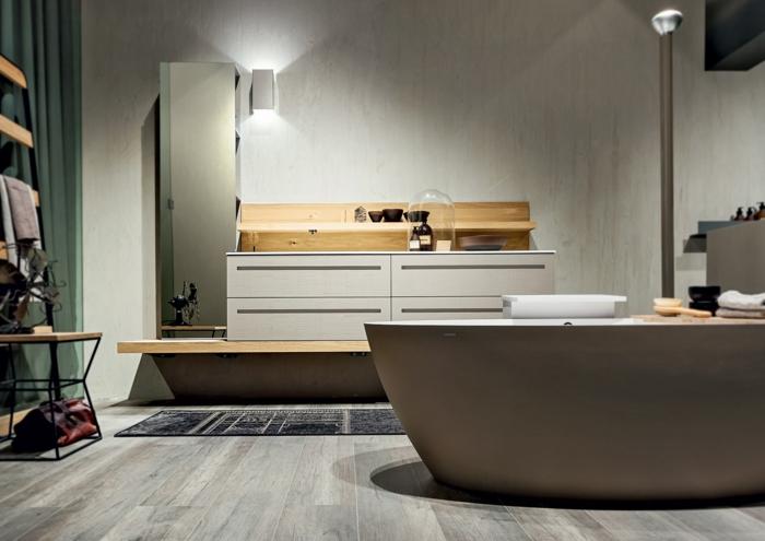 baño moderno pequeño, muebles auxiliares, bañera ovalada, suelo de tarima, armarios de plástico y madera, tapete