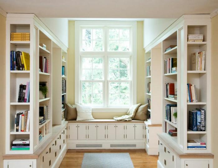 librerias, rincón de lectura cerca de la ventana, armario banco con cojines, estanterías de madera blanca, suelo con parquet y tapete azul