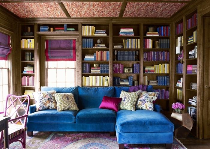 librerias, salón vintage en ciclamen y azul, sofá grande de terciopelo, librería empotrada de madera rustica, ventana con corina, alfombra