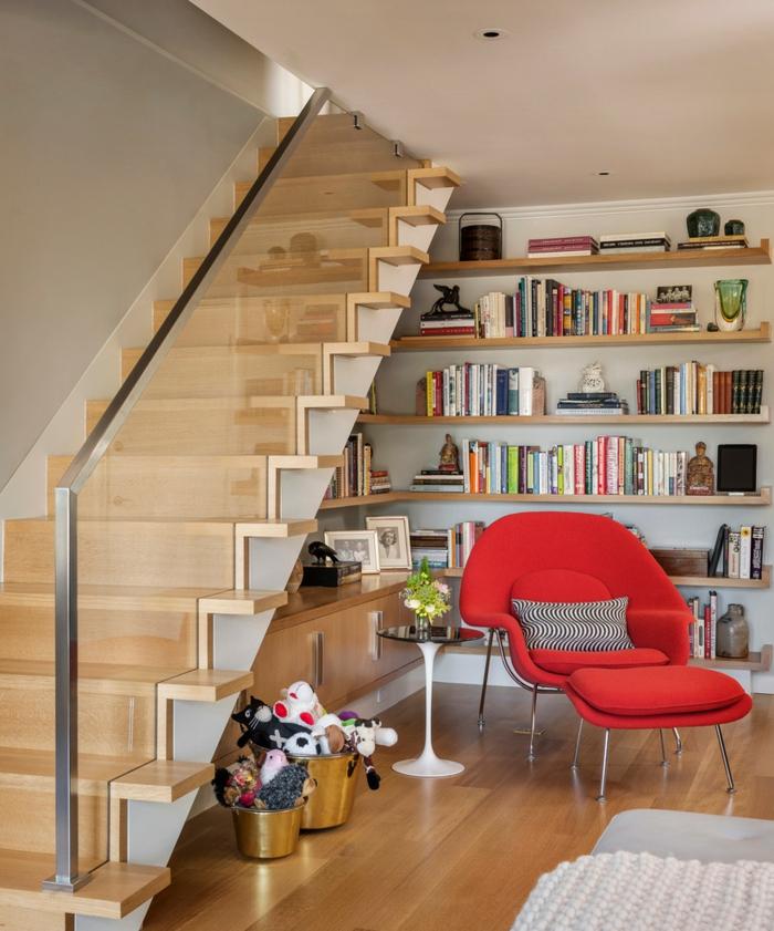 rincón de lectura bjo una escalera con barandilla de vidrio, estantes de madera con libros y decoraciones, sillón rojo con cojin an blanco y negro, librerías