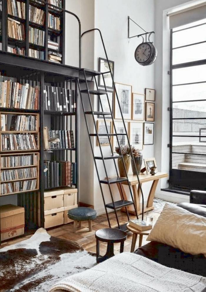 diseño de interiores, baldas de madera, salón moderno con reloj de estación, suelo con parquet, ventana grande, librería alta con escalera de metal, alfombra piel de vaca