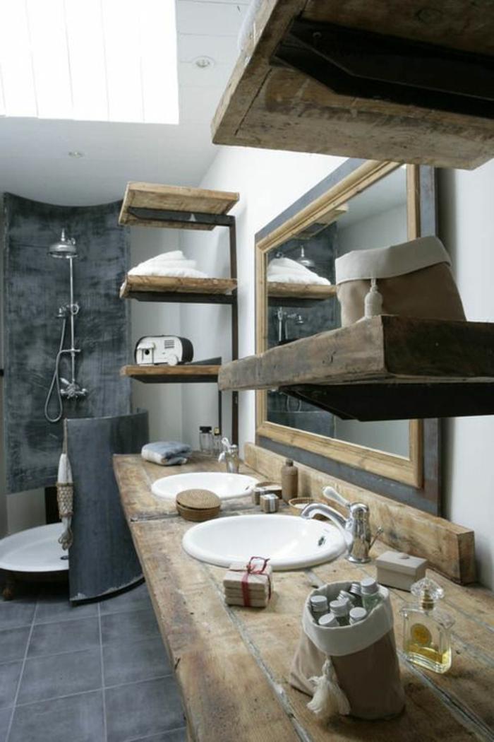 cuartos de baño rusticos con estanterías de madera, paredes de hormigón y suelo con bañdosas en gris, grande espejo con marco de madera