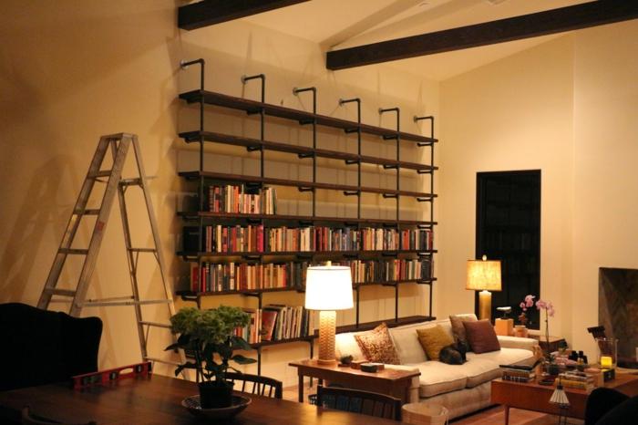 salón en estilo industrial, estanterias de madera, librería de madera y tubos de metal, decoración simétrica, sofá blanco con cojines, mesa de madera, escalera de metal