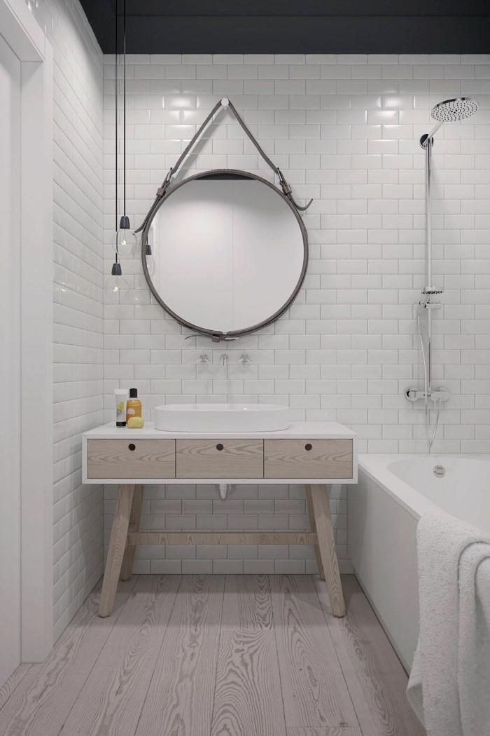 decoración minimalista, pared de ladrillo visto blanco, bañera, muebles auxiliares de baño, cajones de madera, espejo grande redondo