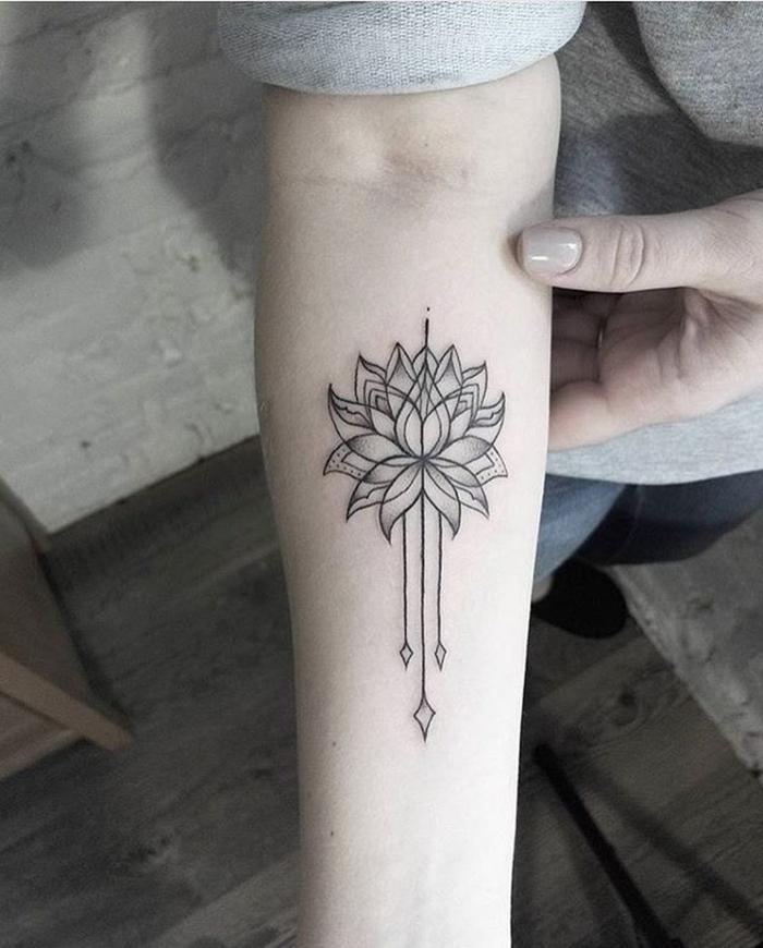 tatuaje flor de loto, tatuaje en blanco y negro, antebrazo mujer, flor de loto abierta con tres flechas