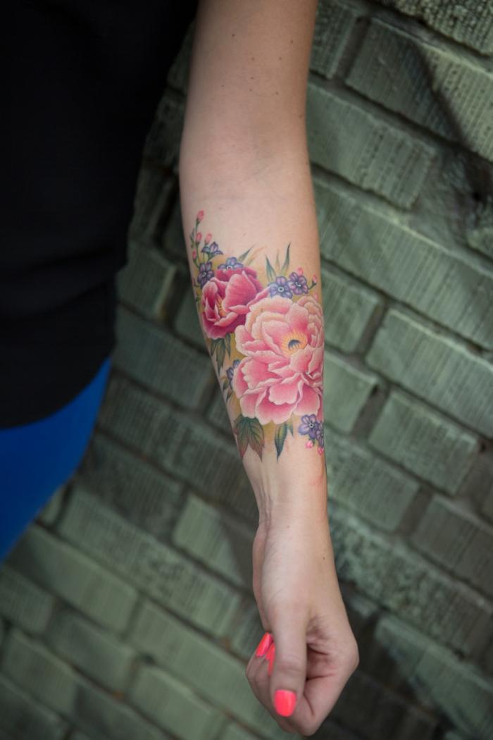 tatuajes de flores, mujer con esmalte en las uñas, tatuaje grande en el antebrazo, crisantemos en rosado con hojas verdes