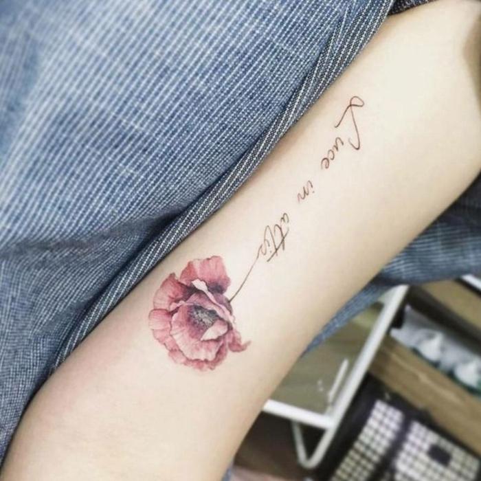 tatuaje acuarela, tatuaje femenino en la parte interna del brazo, amapola roja con tallo con frase en cursiva negro