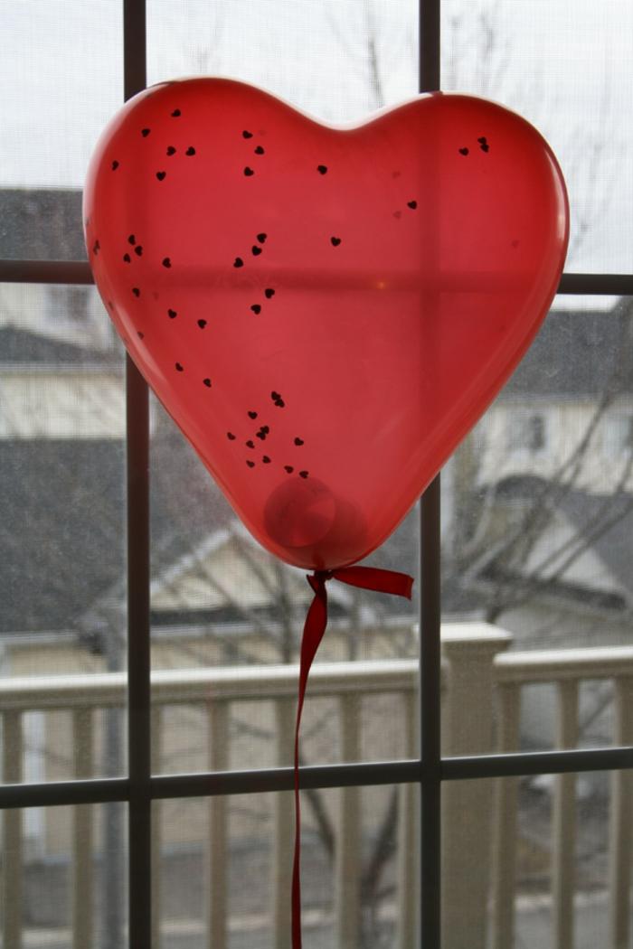 sorpresas romanticas para tu pareja, globo en color rojo con un mensaje romántico dentro, ideas inspiradoras para el 14 de febrero
