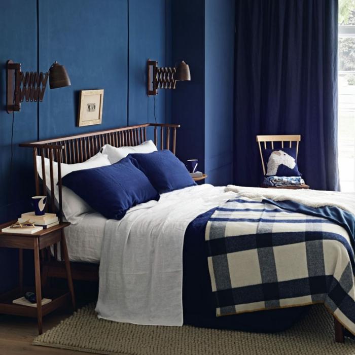 colores habitacion atrevidos, ambiente en azul oscuro, pequeño cuadro decorativo encima de la cama, lámparas vintage