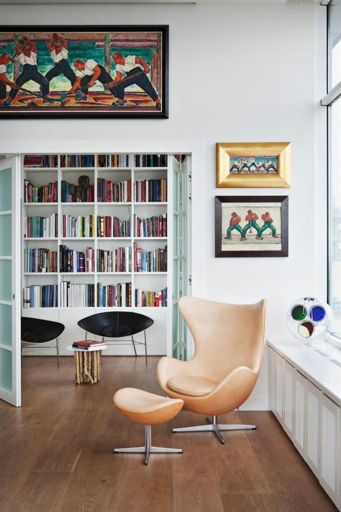 librerias, idea de ecoración con librería grande de madera blanca, puertas con vidrio, sillón moderno tapizado con taburete, cuadros con obreros