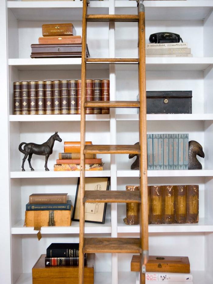 decoración con librería de madera blanca, libros antiguos, estatua de caballo, escalera de madera de mano, estanterias originales,