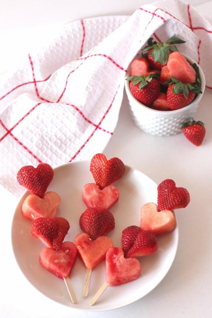 pequeño desayuno hecho de frutas cortadas en forma de corazón, sorpresas románticas con fresas y sandia