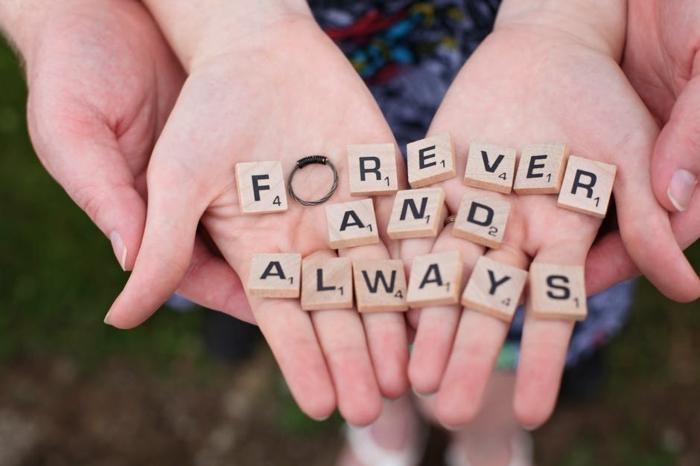 mensaje de amor con pequeños cuadros de madera con letras y cifras, sorpresas románticas con anillo de compromiso
