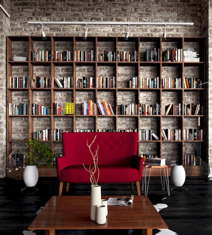 salón con ladrillo visto, estanterias de pared, librería grande de madera, sillón tapizado rojo, elementos vintage, planta verde, maceta blanca