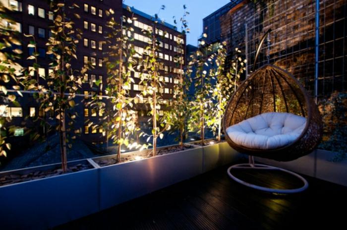 propuesta bonita de una pequeña terraza, barandilla de cristal, pequeños árboles decorativos, silla de mimbre colgante