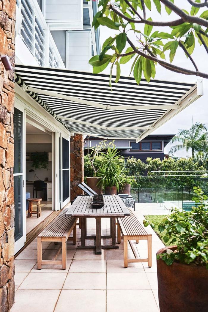 propuesta fresca con motivos marineros, marquesina con estampado de rayas en blanco y azul oscuro, terrazas decoracion con plantas verdes
