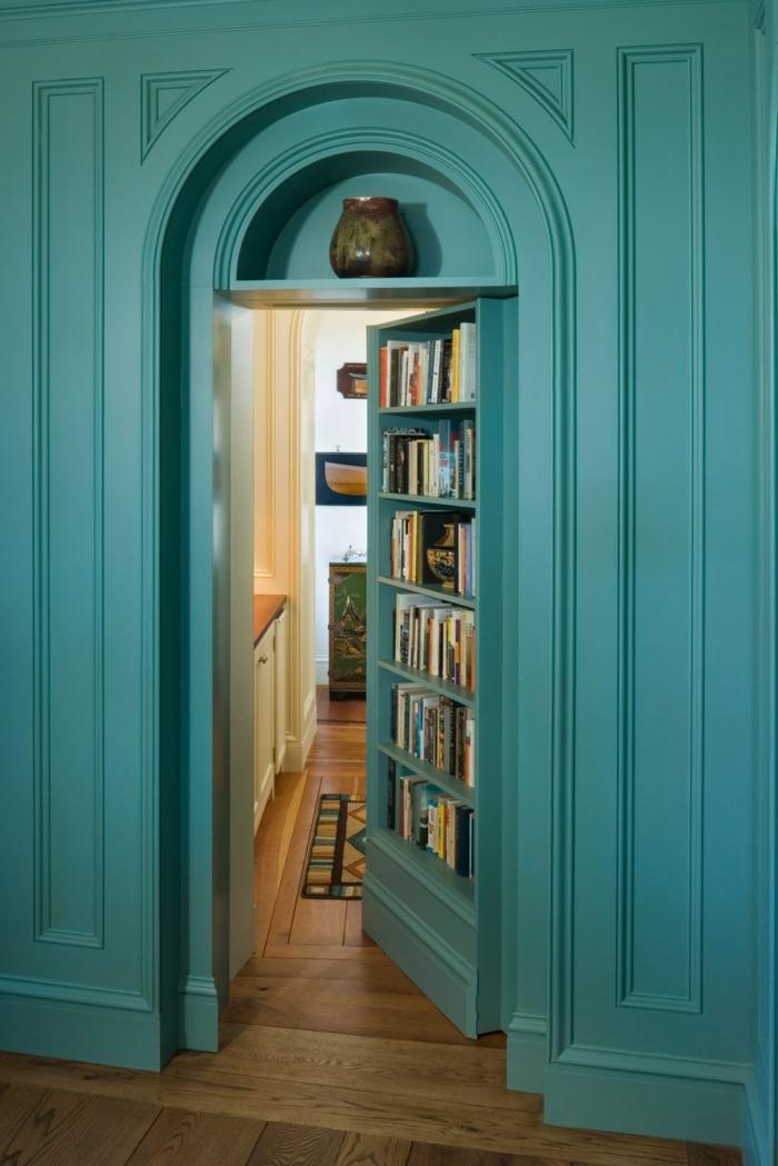 librería empotrada en una puerta, estanterias de pared, pared con madera, entrada a habitación, color turquesa, jarrón decorativo