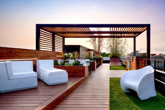 terrazas modernas con pérgola grande, sillones de diseño moderno en blanco, suelo de parquet, decoración de flores y césped corta