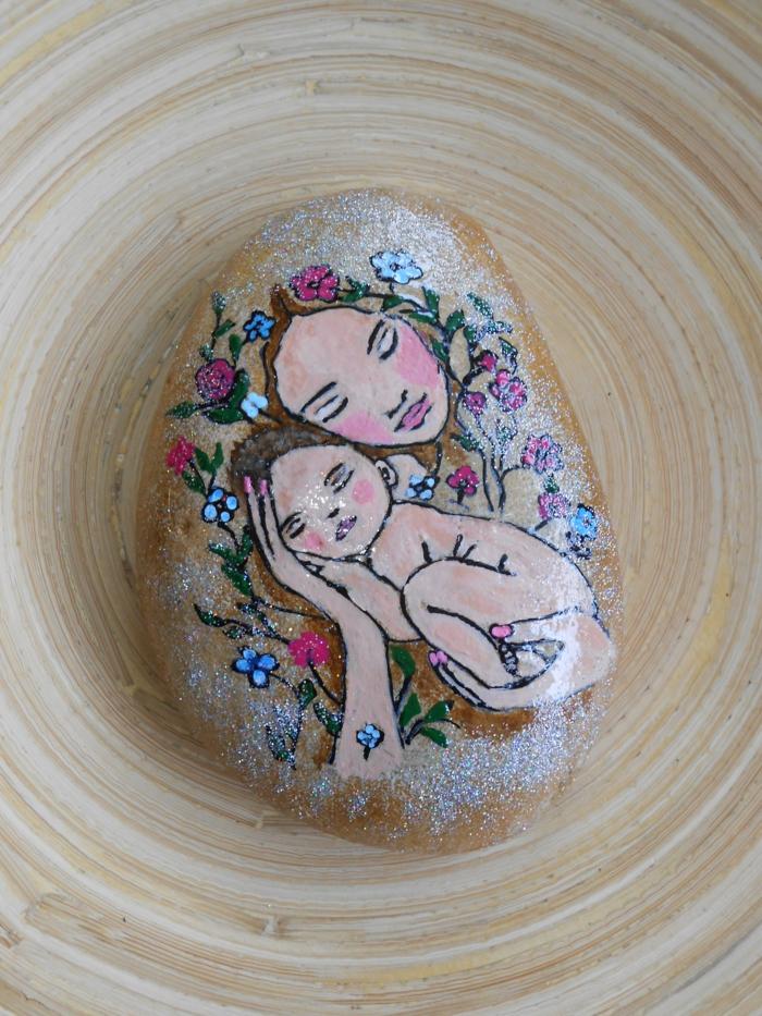 pintar con acrilico, arte sobre piedra, dibujo de madre con su bebe y corona de flores, color rosado con purpurina, manualidades decorativas