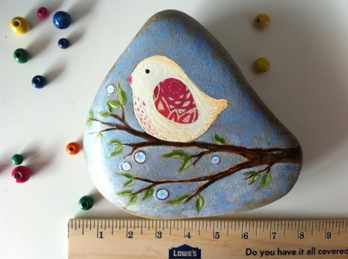 pintar con acrilico, piedra pintada de forma irregular, fondo azul, pájaro sobre una rama, lentejuelas