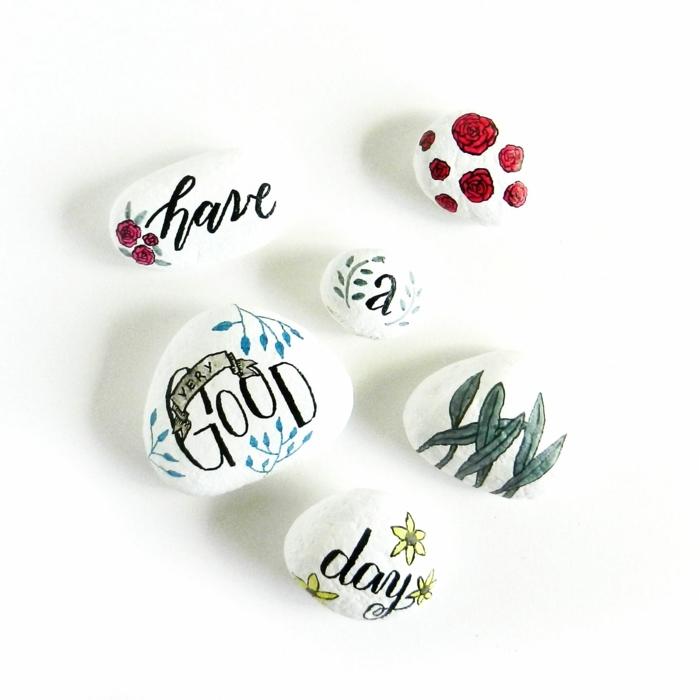 pintar con acrilico, piedras pintadas todo bлаnco, composición de piedras con frase inspiradora en cursiva, rosas y plantas