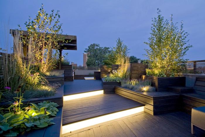 terraza nivelada con lámparas empotradas, pergola de madera grande, terrazas modernas con muchas plantas decorativas