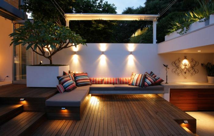 diseño de terrazas modernas decoradas en estilo contemporáneo, suelo de madera, grande macetero con planta verde y lámparas empotradas