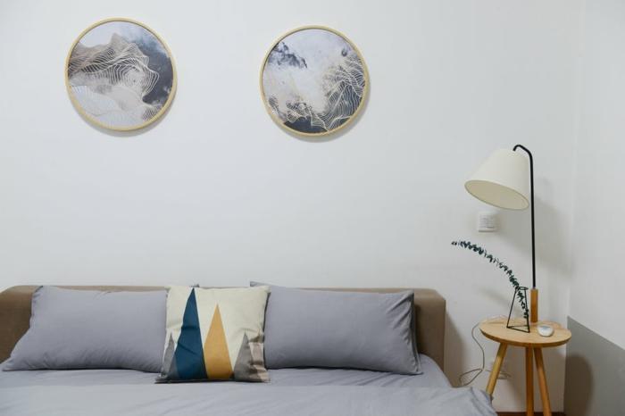 como escoger las colores para el dormitorio, cama doble y mesilla de madera, paredes en blanco decorados de cuadros decorativos en forma oval