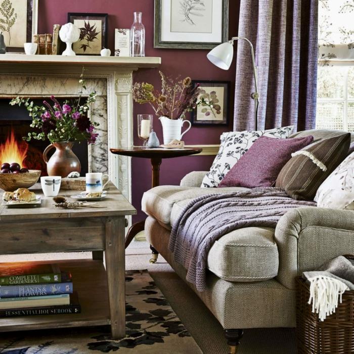 decoración clásica, pinturas para salones, chimenea encendida, sofá gris con cojines y manta, pared en morado con cuadros, mesa de madera con tazas y libros