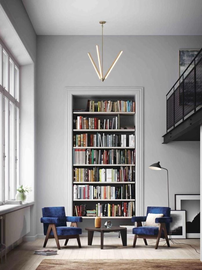 salón con techo alto, suelo con tarima, alfombra marrón, mesita y sillones azules, librería empotrada alta, librerias, pared gris