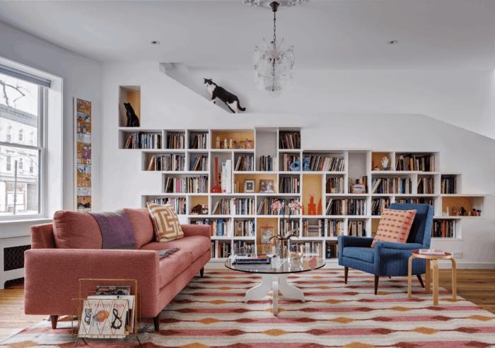 librerías, salón con lñampara de araña, gato en blanco y negro, rosado y azul, estantería empotrada de obra y madera con libros, mesa redonda y alfombra