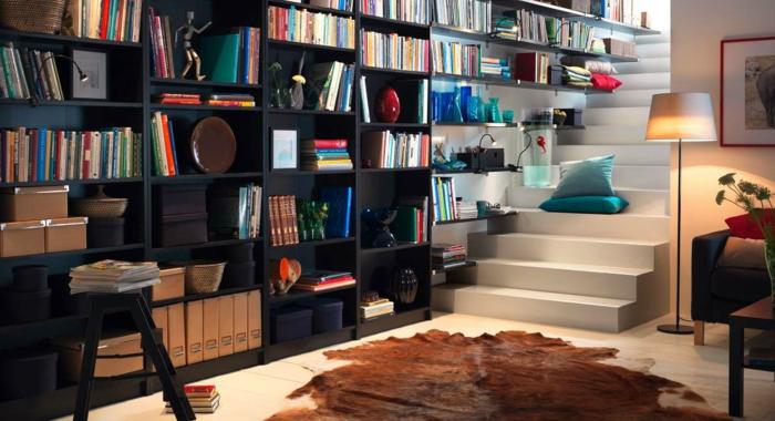 piso con escalera de obra, tapete piel de vaca, estanteria escalera, librería de madera negra, vojines azules, luz artificial