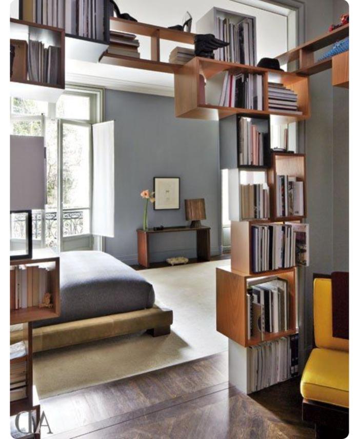 separador de ambientes, estanterias de madera, librería modular, dormitorio con ventana abierta, suelo laminado y alfombra beige