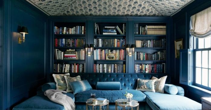 decoracion salon en azul, estanterias originales, sofá tapizada de terciopelo, librería de madera masiva de suelo a techo, techo con papel pintado