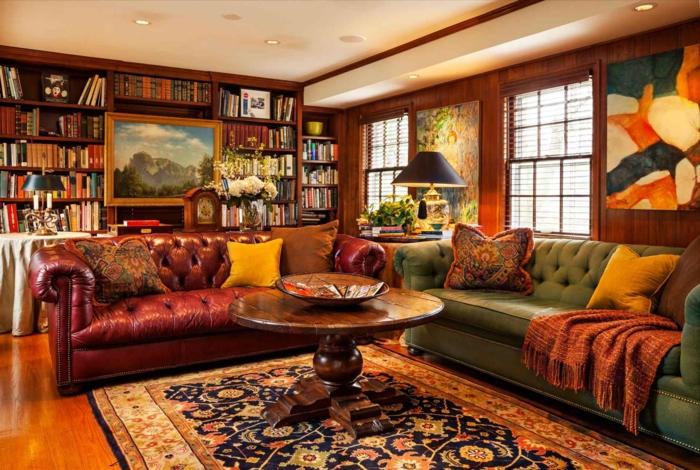 salón de lujo, estanterias originales, librería de suelo a techo con pintura de paisaje, sofás tapizados de piel en capitoné, mesa redonda de madera, alfombra, ventanas con persianas, paredes con madera, luces empotradas en el techo