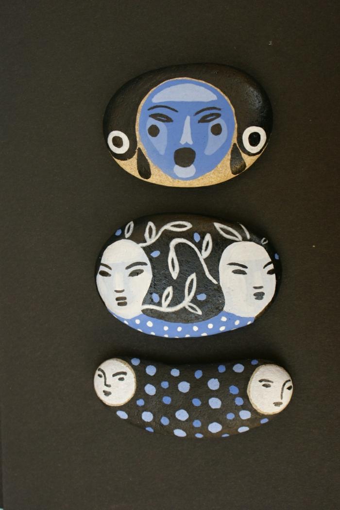 piedras pintadas a mano, arte con piedras pintadas, imagenes de personajes japoneses con dos caras, negro, azul y blanco