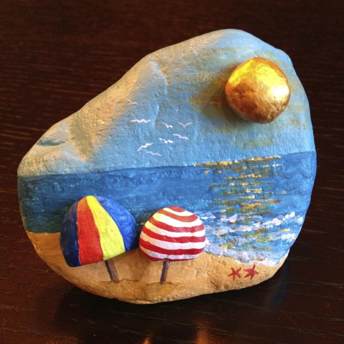 piedras pintadas a mano, manualidades para decorar, paisaje de la playa pintado en piedra, sol dorado, sombrillas con relieve