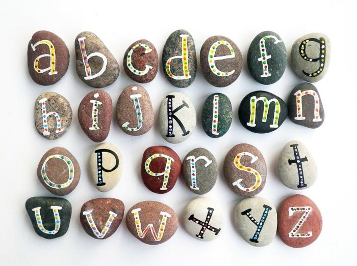 piedras pintadas a mano, composición con piedras de diferente color, alfabeto latino con letras hechas con pintura acrilica, manualidades para niños