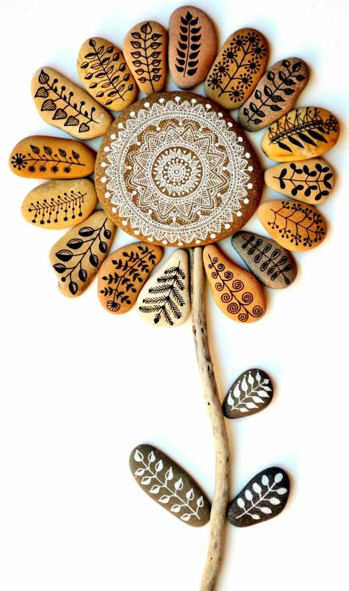 piedras pintadas a mano, composición con pedras pintadas, flor grande con tallo y pétalos, piedras marrones pintadas con hojas en negro y blanco