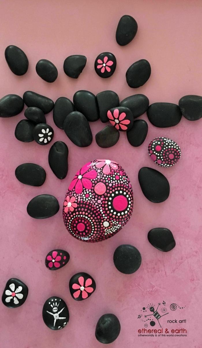 piedras pintadas a mano, piedras planas negras pintadas con puntitos en blanco y flores en rosado, decoración para jardines