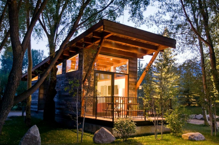 casa cube, vivienda mínima de madera de forma alargada con pequeña terraza con cerco, jardín con muchos árboles jóvenes