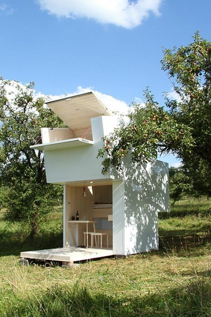 mini casa, preciosa minicasa en blanco hecha de madera con paredes abatibles, ideas para optimizar espacios pequsños