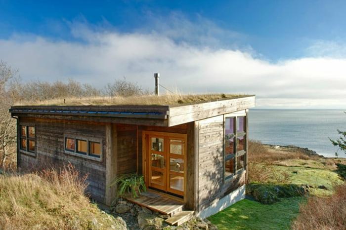mini casas de ensueño, casa en la orilla del mar con diseño simple y forma cuadrada, muchas ventanas de diferente tamaño y forma