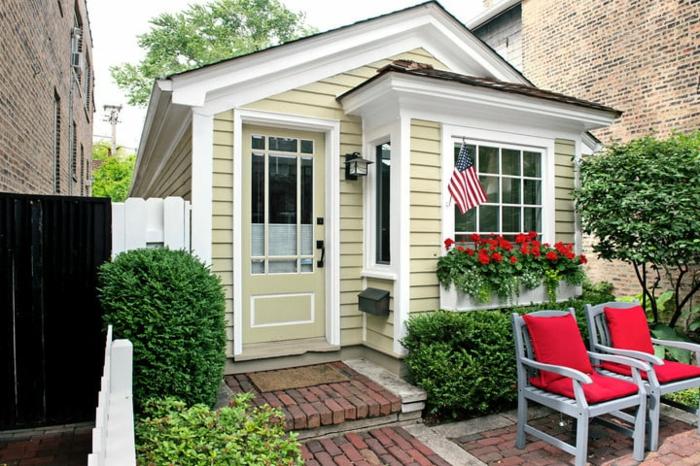 mini casas de ensueño, casa de diseño clásico de pequeño tamaño pintada en color ocre y blanco, pequeño jardín con sillas cómodas