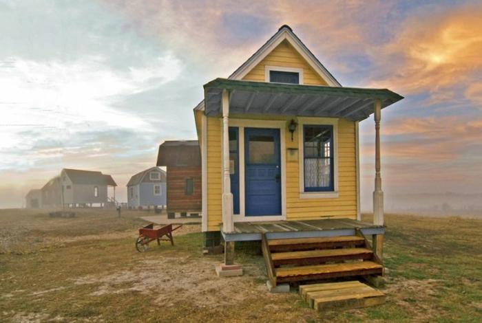 mini casa, pequeña casa en color amarillo con puerta azul, veranda de madera con escaleras, pequeña buhardilla habitable