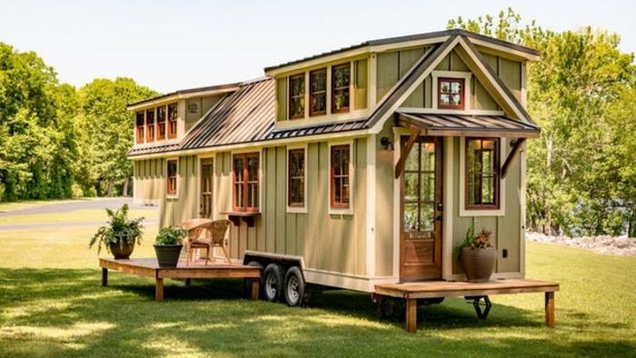 mini casa, casa de tamaño pequeño con interesantes elementos arquitectónico y muchas ventanas, dos plataformas de madera decoradas con flores