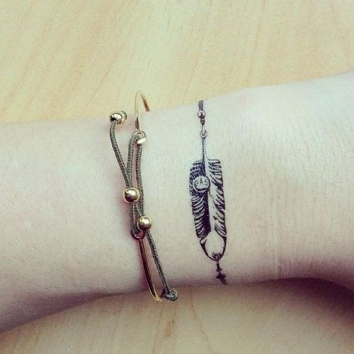 tatuaje minimalista femenino, brazalete de tinte con pluma,. muñeca con pulsera, tatuajes de nombres en la muñeca