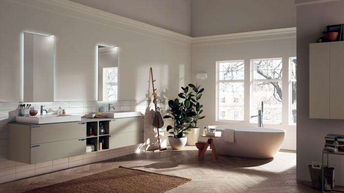 espacio con luz natural baño en tonos neutrales, bañera exenta, baños pequeños, dos lavabos, dos espejos, plantas verdes, tapete, suelo con parquet, ventana grande